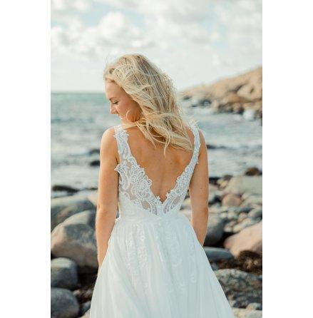 Drömklänning med vacker spets som faller ner över kjolen